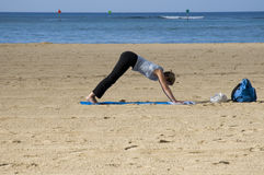 Beach strech. Young woman on beach doing morning exercises royalty free stock photography
