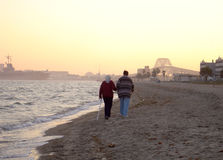 Beach Stroll. Two elderly stroll along a beach at sunset Stock Photo