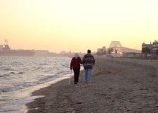Beach Stroll. Two elderly stroll along a beach at sunset stock photo