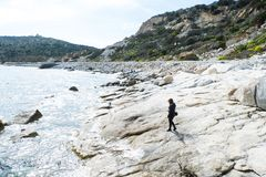 Beach stroll. Girl walk on rocky beach of Capo Carbonara royalty free stock photos