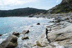 Beach stroll. Girl walk on rocky beach of Capo Carbonara royalty free stock photo