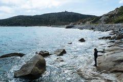 Beach stroll. Girl walk on rocky beach of Capo Carbonara stock photos