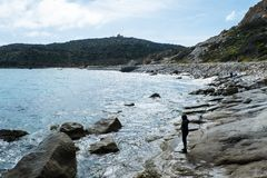 Beach stroll. Girl walk on rocky beach of Capo Carbonara stock image