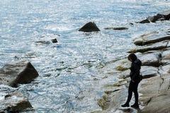 Beach stroll. Girl walk on rocky beach of Capo Carbonara royalty free stock photography