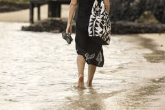 Beach Stroll. A woman walking along the shore in Samoa royalty free stock photography