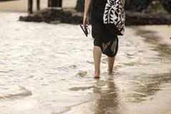 Beach Stroll. A woman walking along the shore in Samoa stock image