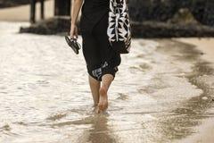 Beach Stroll. A woman walking along the shore in Samoa royalty free stock photo