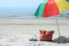 Beach stuff. Beach bag,flipflop and umbrella against blue sea and sand Royalty Free Stock Images
