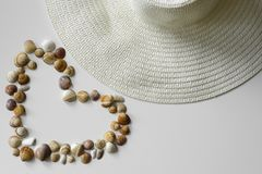 Summer straw hat and heart from seashells. royalty free stock photos