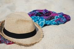 Beach summer accessories on sandy tropical beach. Straw hat, sunglasses and colorfull scarf on sandy tropical beach. Beach Accessories.Vacation concept Stock Photos