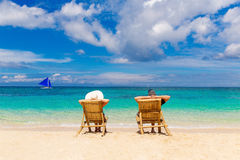 Beach summer couple on island vacation holiday relax in the sun. On their deck chairs on the tropical beach. Idyllic travel background Royalty Free Stock Photo