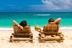 Beach summer couple on island vacation holiday relax in the sun. On their deck chairs on the tropical beach. Idyllic travel background