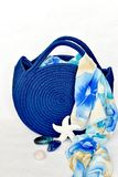 Royal blue knitted beach handbag with floral scarf background royalty free stock photo