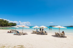 Beach summer on island vacation holiday relax in the sun under u. Blue Bay, Mauritius - December 27, 2015: People relax under umbrellas and in the sun on the Royalty Free Stock Image