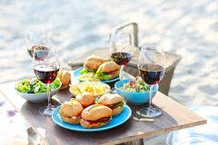 Picnic table with red wine glasses. Beach summer picnic table with red wine glasses royalty free stock photography