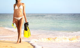 Beach summer travel holidays vacation concept. With woman in bikini walking on sunny beach holding snorkeling equipment, fins and mask. Photo from Makena Beach stock photos