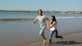 Beach summer vacation couple running on holidays. Happy fun beach vacations couple walking together laughing having fun. On travel destination. Playful stock video footage