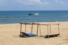 Beach sun beds blue ocean fishing boat, Dong Hoi, Vietnam royalty free stock photography