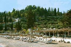 Beach with sun beds. And umbrellas under green hill with cypresses stock photography