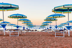 Beach with sun loungers and umbrellas at sunrise.  Royalty Free Stock Images