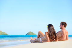 Beach sun tan couple on holiday in Hawaii. Beach sun tan couple relaxing on holiday in Hawaii. Vacations holidays suntan concept - adults lying down tanning on Royalty Free Stock Photography