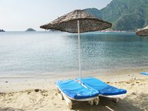 Beach with sun-tents and sun-beds Stock Photos