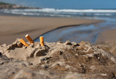 Beach sun and three cigarette butts. Three cigarette butts in the sand on beach with sea in background Stock Photo