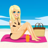 Beach Sunbathing Blonde. Beautiful young happy blonde woman applying suntan cream on her arms sitting in pink towel at beach sunbathing Royalty Free Stock Photography