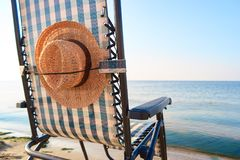 Beach sunbed with fastened woman`s sun hat. Fastened sun hat to a deck chair Stock Images