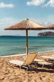 Beach sunbed and parasol overlooking turquoise water Stock Images