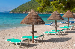 Beach sunbeds. Empty summer beach sunbeds and umbrellas at Majorca (Mallorca) beach resort in Formentor Stock Photography