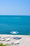 Beach and sunbeds. Pebble Beach and sunbeds on the Black Sea. Clear Sky Stock Photos