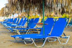 Beach Sunbeds With Straw Umbrellas. Sandy Beach with sunbeds and with straw umbrellas in Crete, Greece stock photography