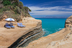 Beach sunbeds and umbrella on a cliff above the blue sea Stock Images