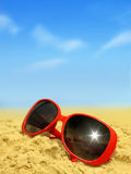 Beach and Sunglasses. Dark tinted sunglasses reflecting sun on  beach Royalty Free Stock Photos