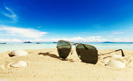 At the beach. Sunglasses at the beach with ocean in background stock image