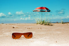 Beach sunglasses umbrella sea and sky Royalty Free Stock Images