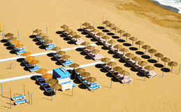 Beach with sunlounger and umbrellas Stock Image
