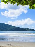 Beach in sunny day with blue sea and island in the background. View of quiet beach in sunny day with blue sea and island in the background Stock Photo