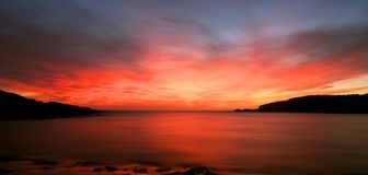 Beach sunrise. Sunrise over a bay with a red sky Royalty Free Stock Image