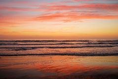Beach sunrise. Intense red, pink and blue colors in the sky and reflected on the beach sand on South Padre Island, Texas stock photos
