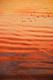Beach with sunrise colors. Intense red and orange colors reflected on the beach sand on South Padre Island, Texas. This shot would be wonderful for a background royalty free stock photography