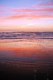 Beach with sunrise colors. Intense red, pink and blue colors in the sky and reflected on the beach sand on South Padre Island, Texas royalty free stock image