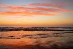 Beach with sunrise colors. Intense red, pink and blue colors in the sky and reflected on the beach sand on South Padre Island, Texas stock photography