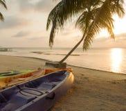 Beach Sunrise With Kayaks. Kayaks sitting on the beach at dawn with a beautiful sunrise Stock Photo