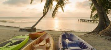 Beach Sunrise With Kayaks. Kayaks sitting on the beach at dawn with a beautiful sunrise Stock Photography