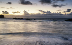 Beach sunrise landscape with long exposure waves movement Stock Images
