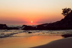 A beach sunrise. A man on the rocks at a beach sunrise Royalty Free Stock Image
