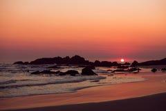 A beach sunrise. Rocks at a beach at sunrise sunrise Stock Photos