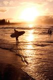 Beach sunset. A surfer walks in from an afternoon surfing royalty free stock photography